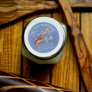 beautiful jar of spoon butter with a grey label, white lettering. Butter is framed by beautiful handmade wooden tools.