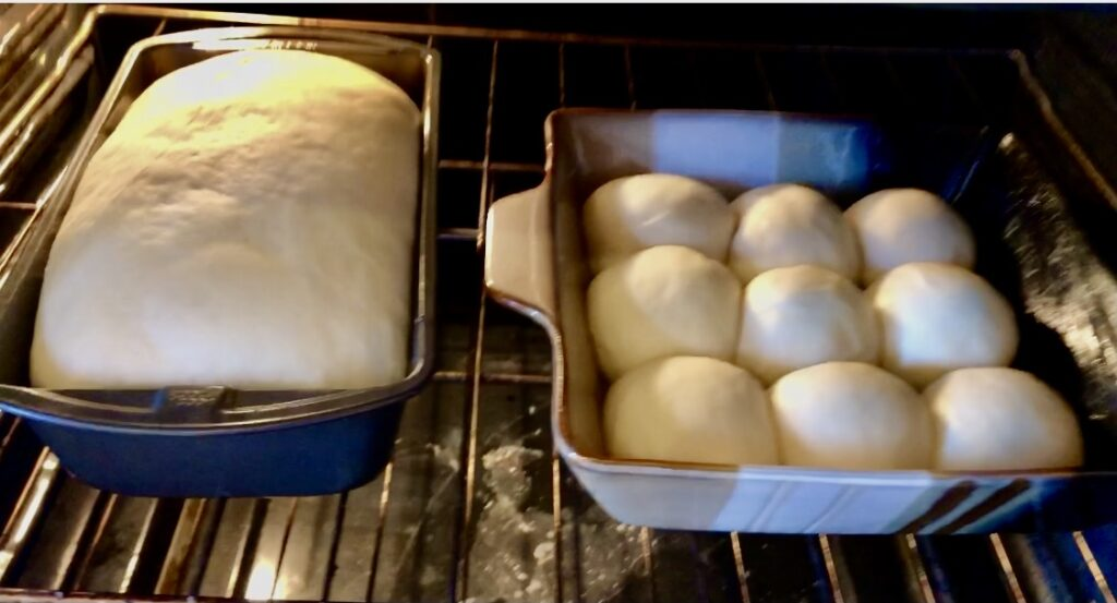 beautifully puffed, risen loaf of traditional homemade white bread and a pan of 12 rolls waiting to be baked.